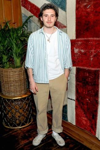 Как и с чем носить: голубая куртка-рубашка в вертикальную полоску, белая футболка с круглым вырезом, светло-коричневые брюки чинос, белые низкие кеды из плотной ткани
