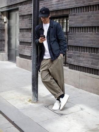 Темно-синяя куртка-рубашка: с чем носить и как сочетать мужчине: Темно-синяя куртка-рубашка в паре с серыми брюками чинос вне всякого сомнения будет обращать на себя взгляды красивых девушек. Почему бы не привнести в этот образ немного беззаботства с помощью белых низких кед из плотной ткани?