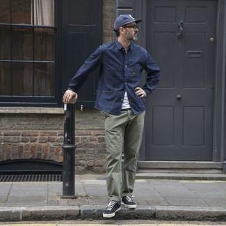 Темно-синяя куртка-рубашка: с чем носить и как сочетать мужчине: Сочетание темно-синей куртки-рубашки и оливковых брюк чинос поможет выглядеть модно, но при этом выразить твою индивидуальность. Пара черно-белых низких кед из плотной ткани добавит луку расслабленности и динамичности.