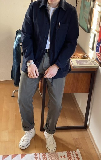 Мужские луки весна: Темно-синяя куртка-рубашка прекрасно сочетается с серыми брюками чинос. Такой ансамбль несложно адаптировать к повседневным реалиям, если дополнить его белыми высокими кедами из плотной ткани. Если ты пребываешь в по-настоящему весеннем настроении, это сочетание вещей окажется под стать.