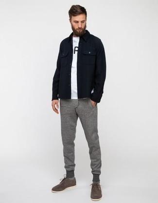 Темно-синяя куртка-рубашка: с чем носить и как сочетать мужчине: Несмотря на то, что это достаточно легкий образ, сочетание темно-синей куртки-рубашки и серых спортивных штанов неизменно нравится стильным молодым людям, покоряя при этом сердца прекрасных дам. Любители экспериментировать могут закончить лук серыми замшевыми туфлями дерби, тем самым добавив в него чуточку строгости.