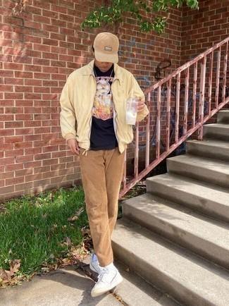 Мужские луки: Темно-синяя футболка с круглым вырезом с принтом и светло-коричневые брюки чинос — великолепный вариант для простого, но модного мужского образа. Белые низкие кеды из плотной ткани великолепно впишутся в образ.
