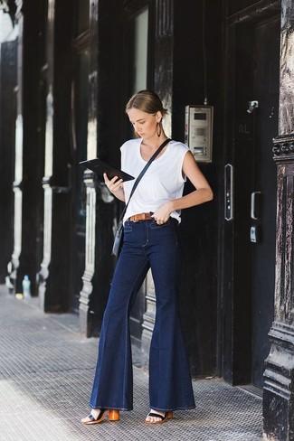 Как и с чем носить: белая майка, темно-синие джинсы-клеш, черные кожаные босоножки на каблуке, темно-синяя кожаная сумка через плечо