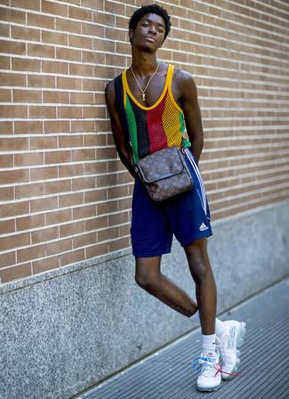 Как и с чем носить: разноцветная майка в сеточку, синие спортивные шорты, белые кроссовки, темно-коричневая кожаная сумка почтальона с принтом