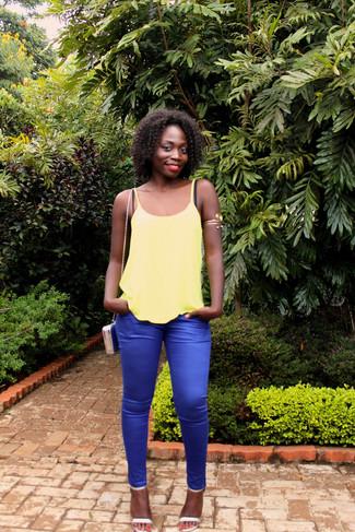 Как и с чем носить: желтая майка, синие узкие брюки, серебряные кожаные босоножки на каблуке, синяя кожаная сумка через плечо