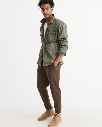 Как и с чем носить: оливковая куртка в стиле милитари, белая футболка с круглым вырезом, коричневые спортивные штаны, светло-коричневые замшевые ботинки дезерты
