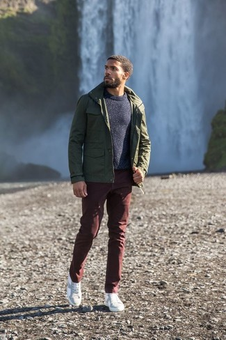 Как и с чем носить: оливковая куртка в стиле милитари, темно-синий свитер с круглым вырезом, темно-красные брюки чинос, белые кожаные низкие кеды