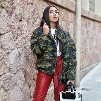 Как и с чем носить: оливковая куртка-пуховик с камуфляжным принтом, бело-черная футболка с круглым вырезом с принтом, красные кожаные брюки-галифе, бело-черная кожаная большая сумка