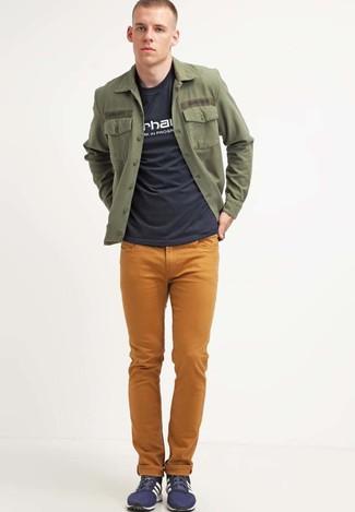 Как и с чем носить: оливковая куртка-рубашка, черно-белая футболка с круглым вырезом с принтом, горчичные джинсы, темно-синие низкие кеды