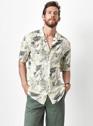 Темно-зеленые шорты: с чем носить и как сочетать мужчине: Оливковая рубашка с коротким рукавом с цветочным принтом и темно-зеленые шорты надежно закрепились в гардеробе современных молодых людей, помогая создавать незаезженные и стильные ансамбли.