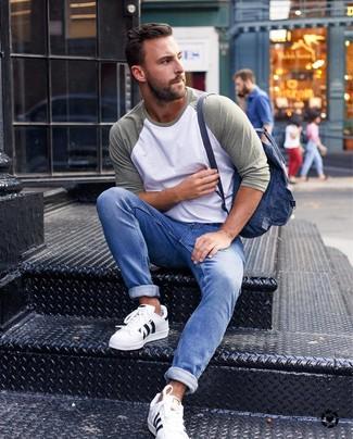 Как и с чем носить: оливковая футболка с длинным рукавом, синие джинсы, белые кожаные низкие кеды, темно-синий рюкзак из плотной ткани