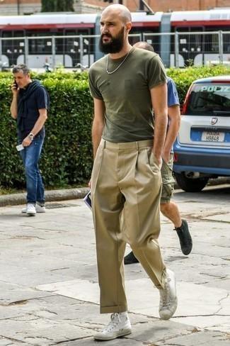 Светло-коричневые классические брюки: с чем носить и как сочетать мужчине: Оливковая футболка с круглым вырезом и светло-коричневые классические брюки — обязательные вещи в гардеробе парней с превосходным вкусом в одежде. Если сочетание несочетаемого привлекает тебя не меньше, чем безвременная классика, закончи этот наряд белыми высокими кедами из плотной ткани.