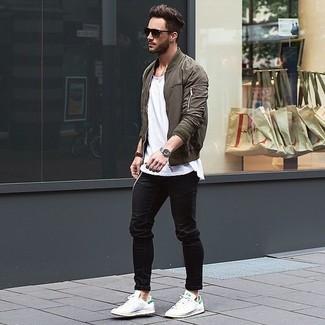 Оливковый бомбер великолепно сочетается с черными джинсами. Что касается обуви, белые низкие кеды станут отличным выбором.