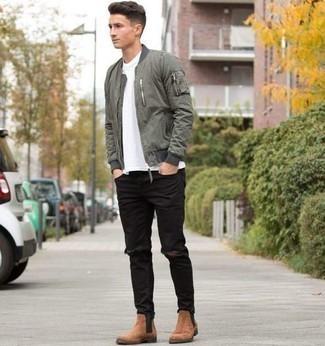 Мода для подростков парней: Оливковый бомбер и черные рваные джинсы — стильный выбор мужчин, которые никогда не сидят на месте. Такой образ обретает свежее прочтение в паре с светло-коричневыми замшевыми ботинками челси.