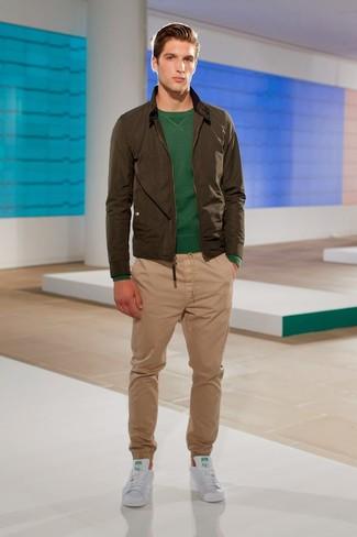 Как и с чем носить: оливковый бомбер, темно-зеленый свитер с круглым вырезом, светло-коричневые брюки чинос, белые кожаные низкие кеды