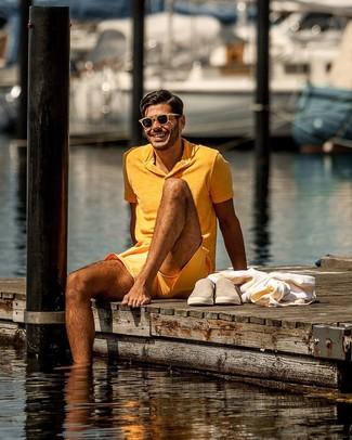 Как и с чем носить: оранжевая футболка-поло, оранжевые шорты, светло-коричневые замшевые слипоны, светло-коричневые солнцезащитные очки