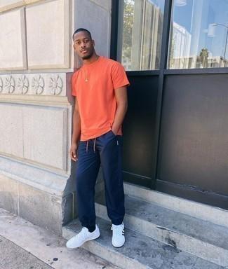 Мужские луки в жару: Если в одежде ты ценишь удобство и функциональность, оранжевая футболка с круглым вырезом и темно-синие спортивные штаны — замечательный выбор для расслабленного мужского ансамбля на каждый день. Дополнив ансамбль бело-черными кожаными низкими кедами, можно получить занятный результат.