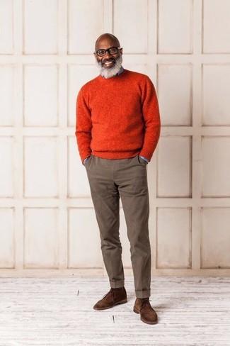 Как и с чем носить: оранжевый свитер с круглым вырезом, голубая джинсовая рубашка, коричневые брюки чинос, коричневые замшевые ботинки дезерты