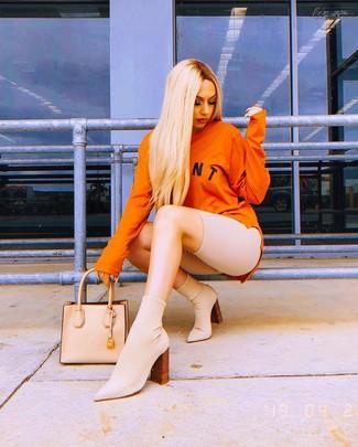 Как и с чем носить: оранжевый свитшот с принтом, бежевые велосипедки, бежевые ботильоны на резинке, бежевая кожаная большая сумка