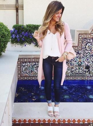 Как и с чем носить: розовый открытый кардиган, белая шелковая майка, темно-синие джинсы скинни, белые кожаные босоножки на каблуке
