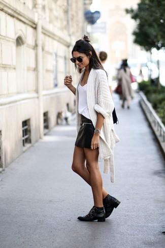Как и с чем носить: белый вязаный открытый кардиган, белая майка, черная кожаная мини-юбка, черные кожаные ботильоны с шипами