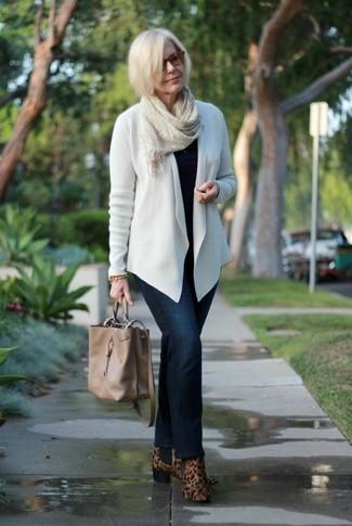 Как и с чем носить: белый открытый кардиган, черный свитер с круглым вырезом, темно-синие джинсы, коричневые замшевые ботильоны с леопардовым принтом