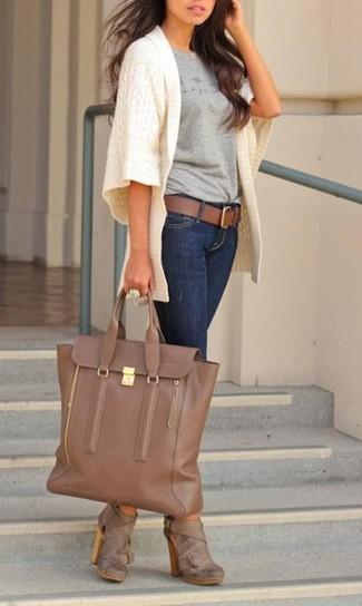 Как и с чем носить: белый вязаный открытый кардиган, серая футболка с круглым вырезом с принтом, темно-синие джинсы скинни, коричневые кожаные ботильоны
