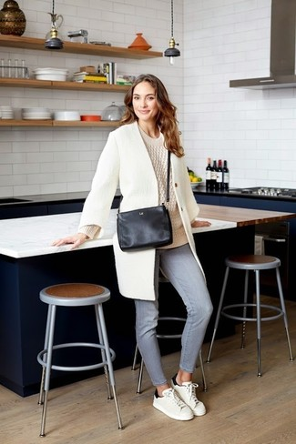 Как и с чем носить: белое пальто, бежевый вязаный свитер, серые джинсы, бело-черные кожаные низкие кеды