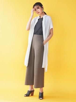 Как и с чем носить: белое пальто дастер, темно-серая футболка с круглым вырезом, коричневые вязаные широкие брюки, черные кожаные сабо