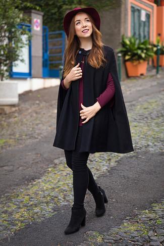 Как и с чем носить: черное пальто-накидка, темно-красная блузка с длинным рукавом, черные джинсы скинни, черные замшевые ботильоны