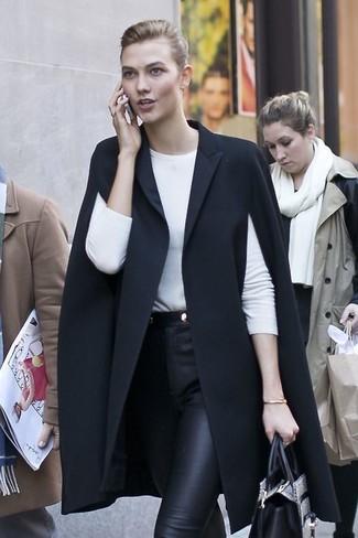 Как и с чем носить: черное пальто-накидка, белая футболка с длинным рукавом, черные кожаные узкие брюки, серая кожаная большая сумка со змеиным рисунком