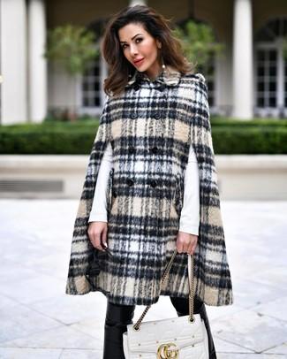 Как и с чем носить: бежевое пальто-накидка в шотландскую клетку, белая футболка с длинным рукавом, черные кожаные узкие брюки, белая кожаная стеганая сумка-саквояж