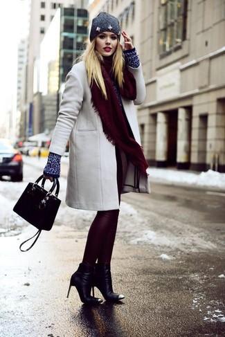 Как и с чем носить: серое пальто, темно-синий свитер с круглым вырезом, темно-красные кожаные леггинсы, черные кожаные ботильоны