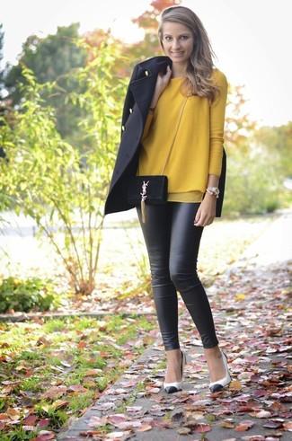 Как и с чем носить: черное пальто, горчичный свитер с круглым вырезом, черные кожаные леггинсы, бело-черные кожаные туфли