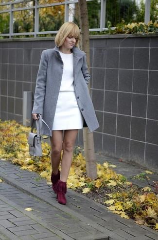 Как и с чем носить: серое пальто, белый свитер с круглым вырезом, белая мини-юбка, темно-красные замшевые ботильоны c бахромой