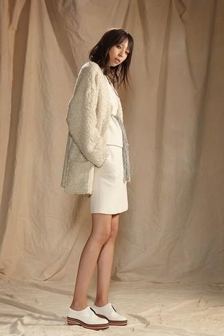 Как и с чем носить: бежевое флисовое пальто, белый свитер с круглым вырезом, белая вязаная мини-юбка, белые кожаные оксфорды