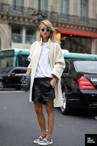 Как и с чем носить: бежевое флисовое пальто, белая футболка с круглым вырезом, черные кожаные шорты, серые слипоны в шотландскую клетку