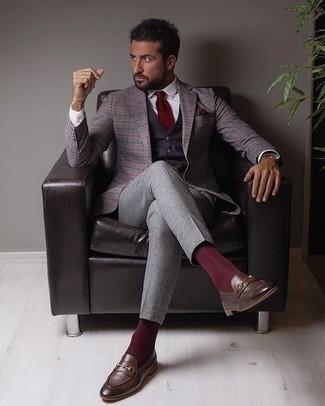 С чем носить пурпурный жилет: Несмотря на то, что это довольно-таки сдержанный ансамбль, сочетание пурпурного жилета и серых классических брюк всегда будет выбором современных джентльменов, покоряя при этом сердца женского пола. Закончив ансамбль темно-коричневыми кожаными лоферами, ты привнесешь в него немного динамичности.