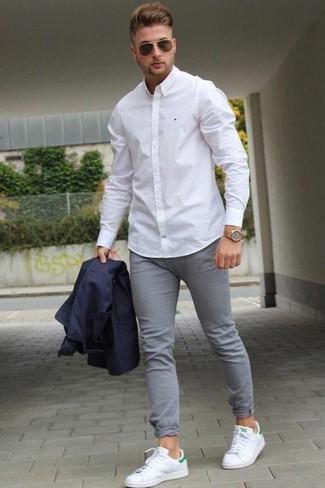 Как и с чем носить: темно-синий пиджак, белая классическая рубашка, серые зауженные джинсы, белые кожаные низкие кеды
