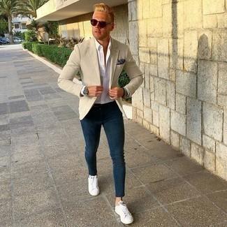 Темно-синие зауженные джинсы: с чем носить и как сочетать мужчине: Бежевый пиджак и темно-синие зауженные джинсы надежно закрепились в гардеробе многих парней, помогая создавать яркие и стильные ансамбли. Белые кожаные низкие кеды — хороший выбор, чтобы дополнить образ.