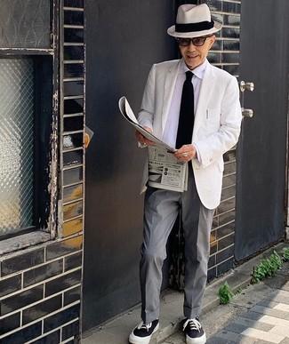 Как одеваться мужчине за 60: Комбо из белого пиджака и серых классических брюк поможет создать незабываемый мужской лук. Поклонники смелых сочетаний могут закончить образ черно-белыми низкими кедами из плотной ткани.