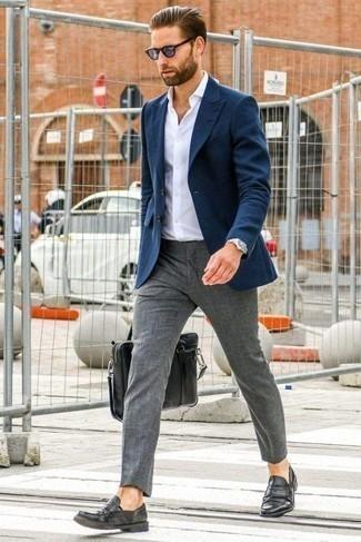 Серые классические брюки: с чем носить и как сочетать мужчине: Несмотря на то, что этот образ выглядит весьма выдержанно, тандем темно-синего пиджака и серых классических брюк всегда будет выбором стильных мужчин, неминуемо пленяя при этом сердца представительниц прекрасного пола. Черные кожаные лоферы чудесно впишутся в ансамбль.