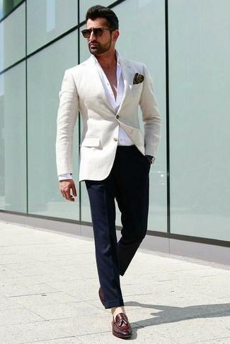 С чем носить бежевый пиджак мужчине: Несмотря на то, что этот лук выглядит довольно сдержанно, сочетание бежевого пиджака и темно-синих классических брюк всегда будет по душе стильным мужчинам, но также покоряет при этом дамские сердца. Темно-красные кожаные лоферы с кисточками удачно дополнят этот лук.