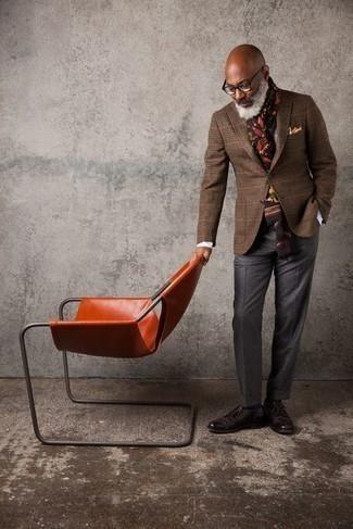 Как одеваться мужчине за 50: Несмотря на то, что это классический ансамбль, ансамбль из коричневого шерстяного пиджака в клетку и темно-серых классических брюк приходится по душе стильным молодым людям, пленяя при этом сердца представительниц прекрасного пола. Переходя к обуви, можно закончить лук темно-коричневыми кожаными туфлями дерби.