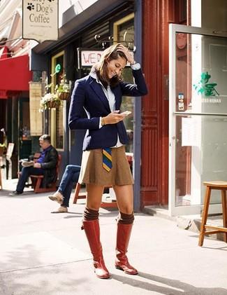 Темно-синий пиджак и табачная мини-юбка без сомнений украсят твой гардероб. Выбирая обувь, сделай ставку на классику и надень красные кожаные сапоги.