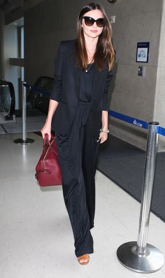 Как Miranda Kerr носит Черный пиджак, Черный комбинезон, Светло-коричневые кожаные босоножки на каблуке, Темно-красная кожаная большая сумка