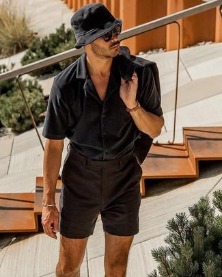 Как и с чем носить: черный льняной пиджак, черная рубашка с коротким рукавом, черные льняные шорты, черная панама