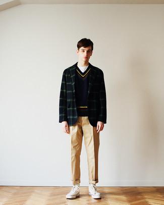 Мода для подростков парней: Дуэт темно-сине-зеленого пиджака в шотландскую клетку и светло-коричневых брюк чинос — хороший пример современного стиля в большом городе. Ты можешь легко адаптировать такой лук к повседневным нуждам, дополнив его белыми высокими кедами из плотной ткани.