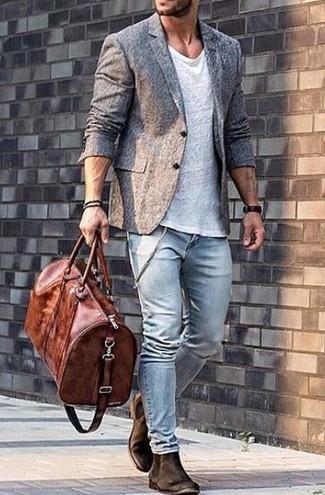 Сочетание белой футболки с круглым вырезом и голубых зауженных джинсов легко вписывается в разные дресс-коды. И почему бы не добавить в этот образ элегантности с помощью темно-коричневых замшевых ботинок челси?