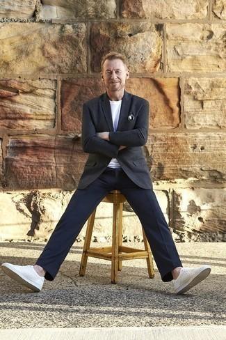 Как одеваться мужчине за 40: Темно-серый шерстяной пиджак и темно-синие классические брюки — олицетворение изысканного мужского стиля в одежде. Чтобы образ не получился слишком строгим, можно дополнить его белыми кожаными низкими кедами.